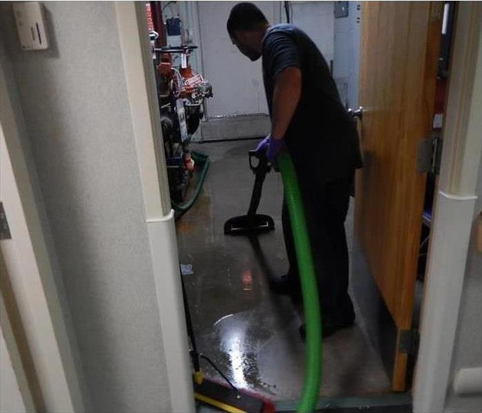 Technician extracting water from concrete floor
